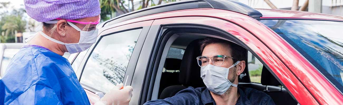 Healthcare workers in masks doing testing by a car.