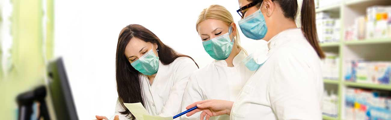 Three female pharmacists wearing masks.