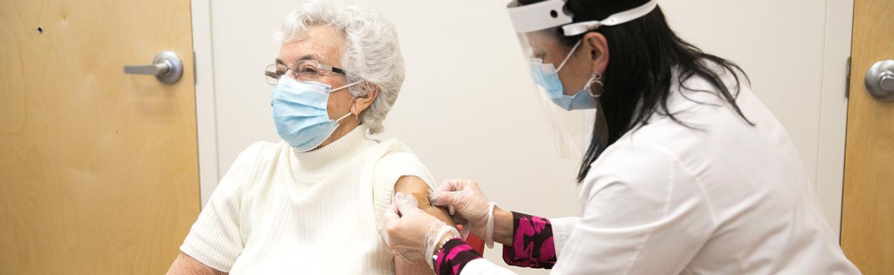 CVS pharmacist giving a senior a vaccine.