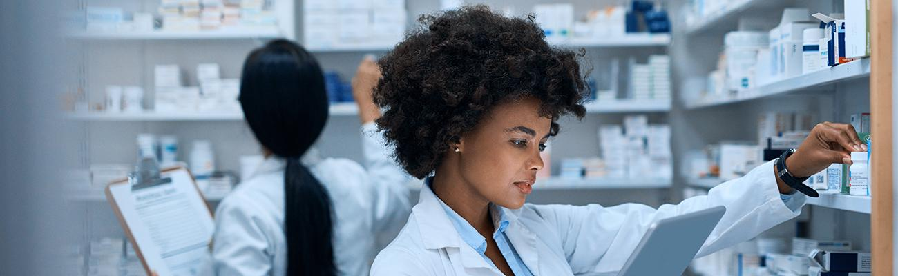 Two female pharmacists in a stock room.