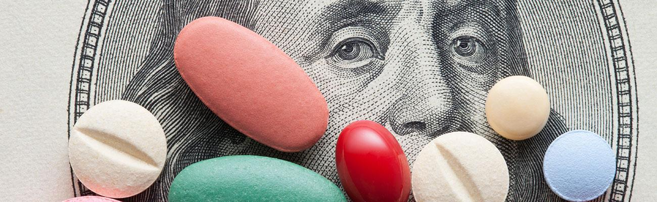 Different colored pills and tablets on the face of money.