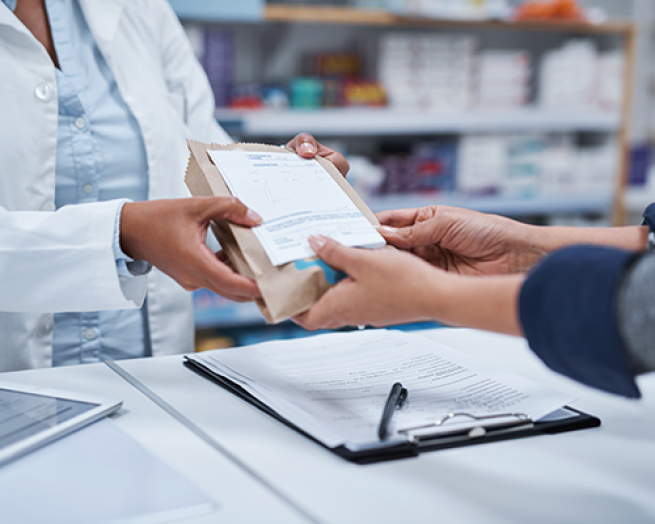 A pharmacist handing a prescription to a patient.