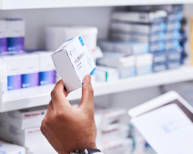 A hand holding a prescription box.