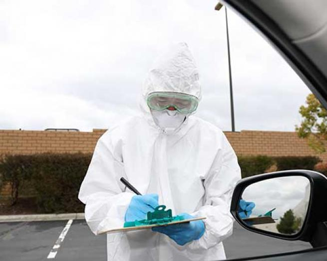 A healthcare worker giving test to a person in a car.
