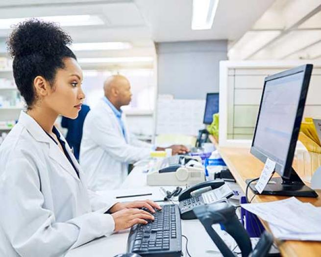 A female pharmacist at a computer.