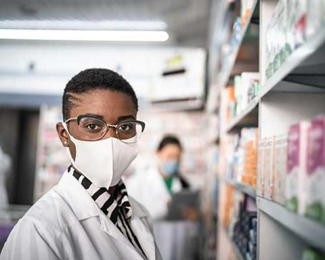 A pharmacist in a mask with a staffer in the background.