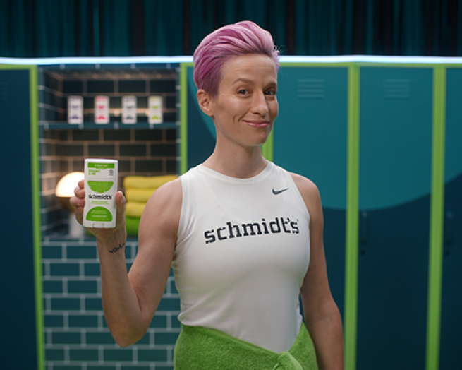 Megan Rapinoe standing in front of a fence