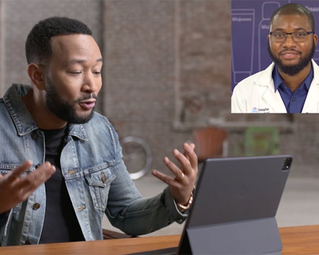 John Legend et al. sitting at a table using a laptop computer