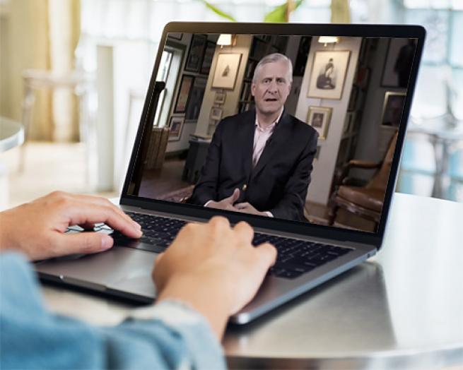 Jon Meacham et al. sitting at a desk and using a laptop computer