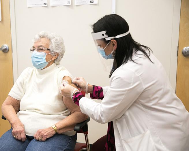 CVS pharmacist giving a senior a vaccine