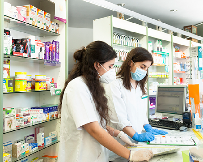 Two pharmacists at a computer in a pharmacy.