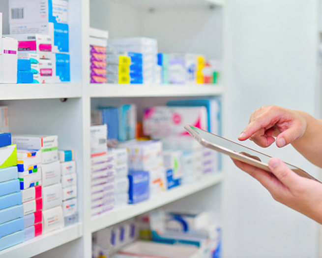 A stockroom filled with medications and a person's hands holding a pad.
