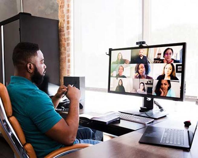 Man sitting a a computer for a virtual meeting.