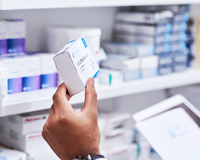 A pharmacist holding a white medication box.
