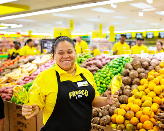 a person standing in front of a store filled with lots of fruit