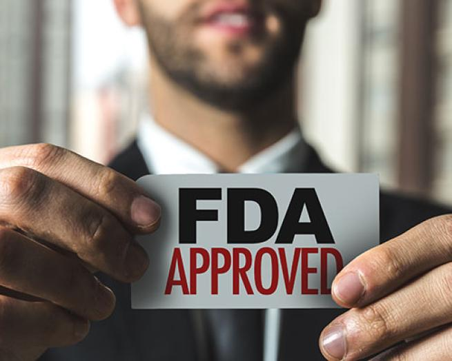 a man holding a sign with the words FDA approved
