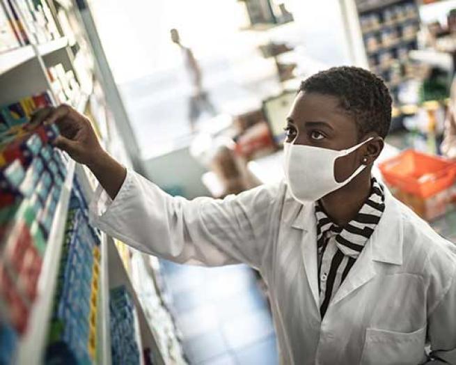A pharmacist wearing a mask taking a medicine off shelf.