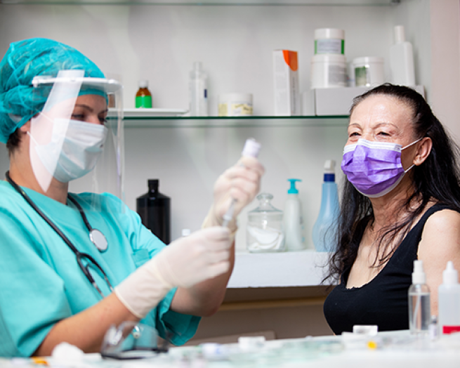 pharmacist getting vaccine ready to give to woman