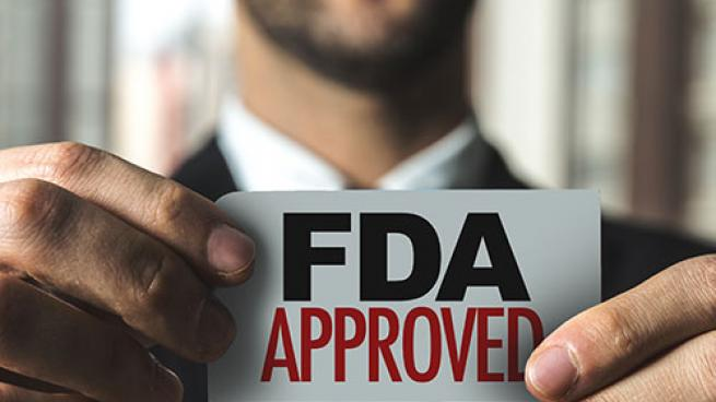 A man holding an FDA approved sign.