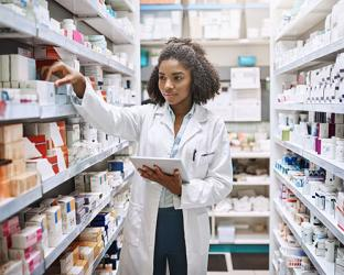 A female pharmacist in a stock room with medications on shelves.