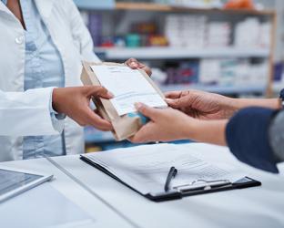 A pharmacist handing a prescription to a patient.