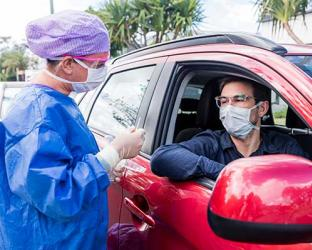 A healthcare worker giving COVID test to a person in a car.