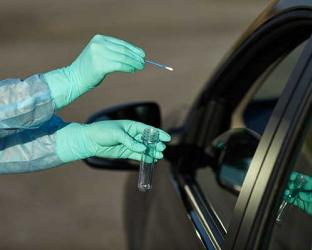 Gloved hands giving COVID-19 test to someone in a car.