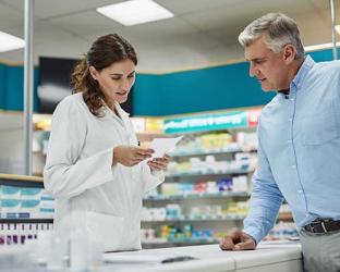 A female pharmacist with a male patient at the counter.