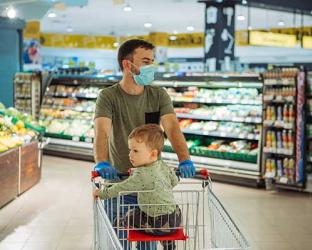 Father wearing mask with baby in supermarket cart.