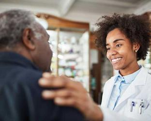 A pharmacist with their hand on a patient's shoulder.