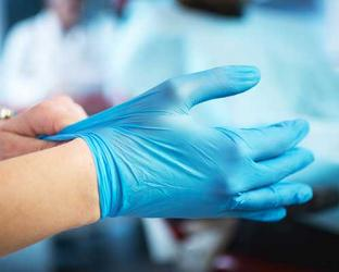 A healthcare worker putting on gloves.