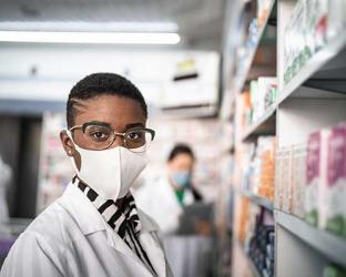 A pharmacist wearing a mask.