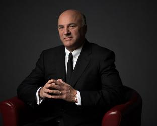 Kevin O'Leary wearing a suit and tie sitting in a chair