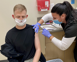A healthcare worker giving a vaccine.