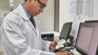 A male pharmacist typing at a computer.